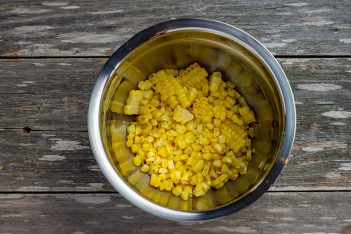 Grilled corn cut off the cob in a stainless steel bowl on a wooden surface