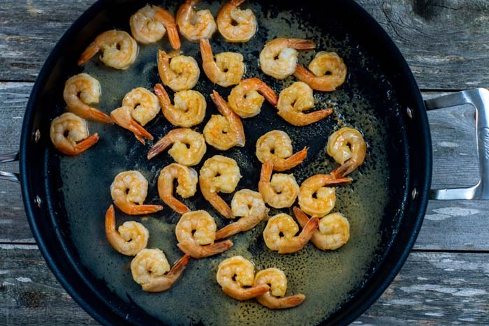 Shrimp cooking in lime juice in a large skillet on a wooden surface