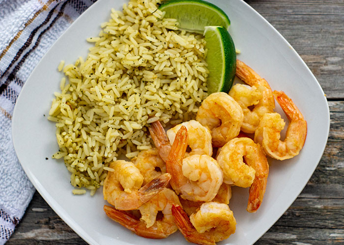 Ginger-lime shrimp next to cilantro and lime shrimp with lime wedges on a square white plate next to a white and brown towel all on a wooden surface