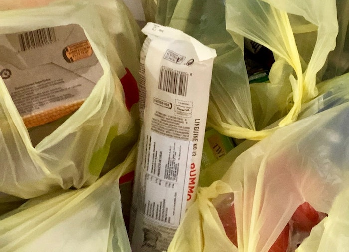 Close up of groceries in yellow plastic bags