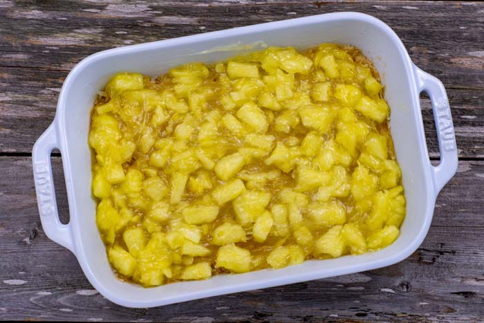 Cooked pineapple in a white casserole dish on a wooden surface