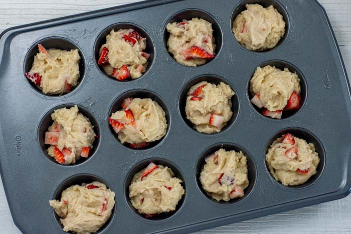 Uncooked strawberry muffin mix in a muffin pan on a white wooden surface