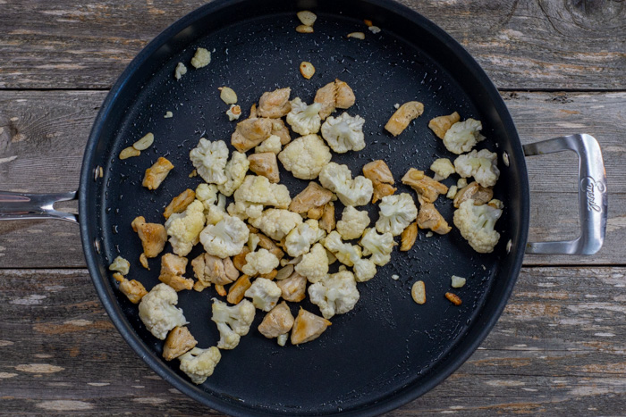 Cooked chicken and cauliflower in a large skillet on a wooden surface