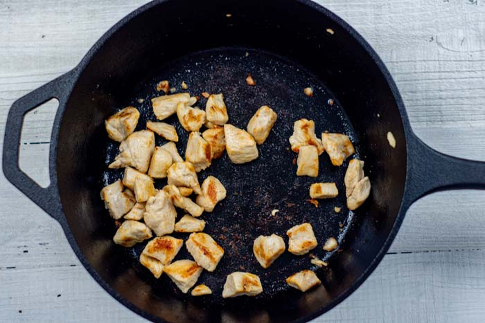 Diced cooked chicken in a cast-iron skillet on a white wooden surface
