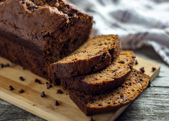 Loaf of chocolate chip banana bread with a few slices cut off on a bamboo tray with a white and brown towel behind all on a wooden surface