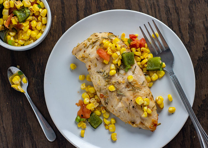 Fresh summer relish on top of a grilled chicken breast with a stainless steel fork on a round white plate with a round white bowl of summer relish behind all on a wooden surface