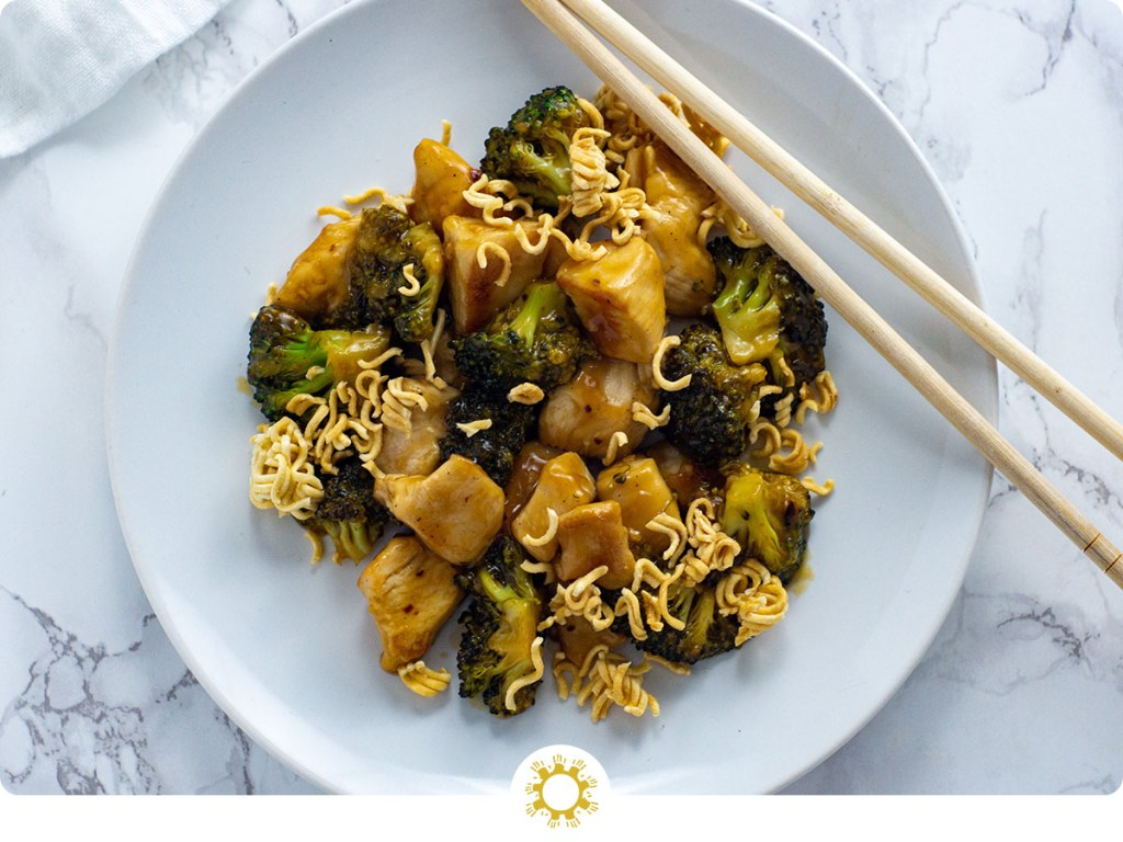 Sweet and Sour Chicken and Broccoli with Ramen Noodles on a round white plate with wooden chopsticks all on a white and grey marble surface (with logo overlay)
