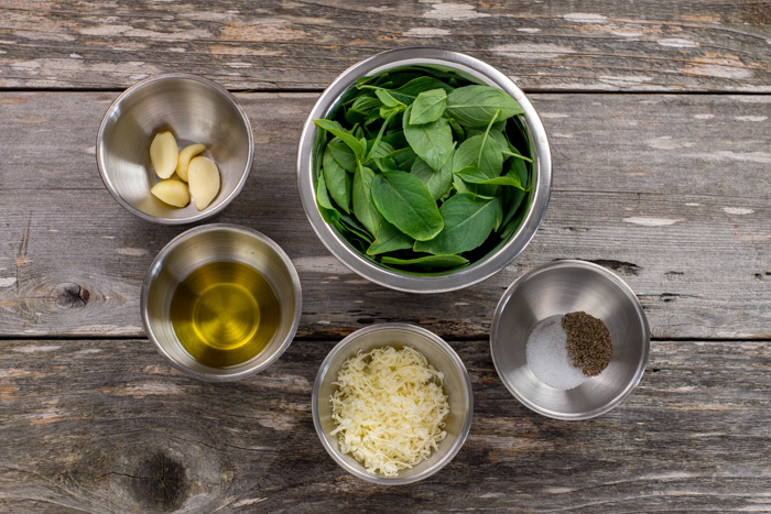 Thai basil pesto ingredients in stainless steel bowls: thai basil leaves, garlic cloves, oil, parmesan cheese, salt, and pepper all on a wooden surface