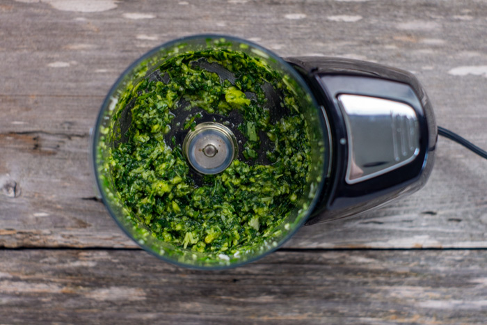 Thai basil pesto in a food processor on a wooden surface