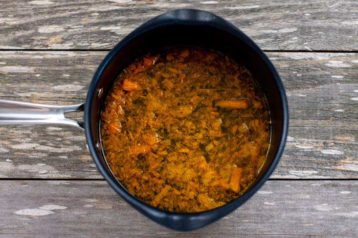 Carrots in liquid in a small saucepan on a wooden surface