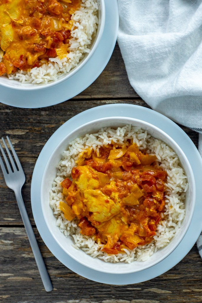 Instant pot butter chicken over white rice in a round white bowl on a round white plate with a stainless steel fork next to a white and gray towel with a second bowl behind all on a wooden surface (vertical)
