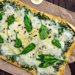 Pesto flatbread topped with shredded cheese and spinach leaves on brown parchment paper on a wooden surface (with title overlay)