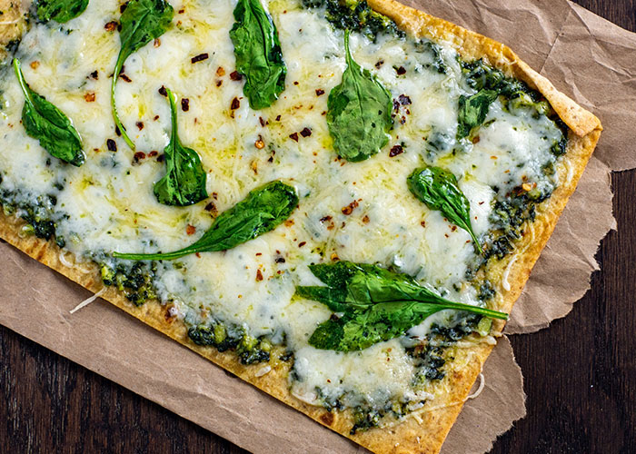 Pesto flatbread topped with shredded cheese and spinach leaves on brown parchment paper on a wooden surface