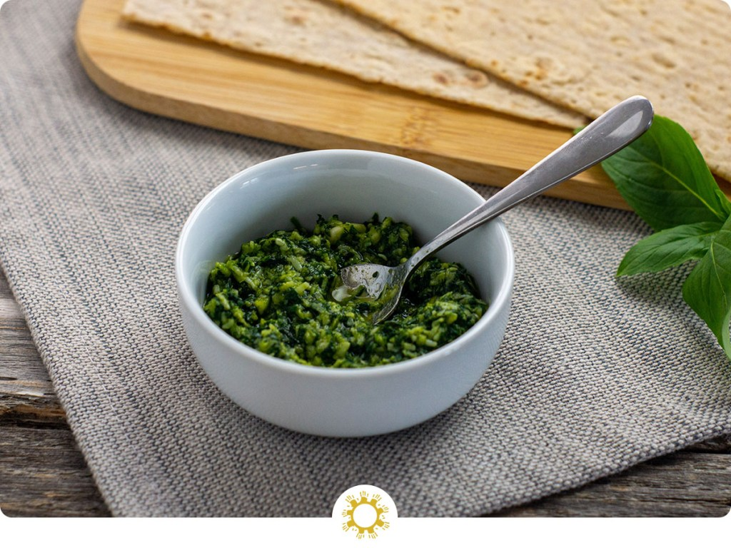 Thai basil pesto in a round white dish with a stainless steel spoon in front of a bamboo board with flatbread next to a sprig of thai basil on a grey placemat all on a wooden surface (with logo overlay)