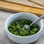 Thai basil pesto in a round white dish with a stainless steel spoon in front of a bamboo board with flatbread next to a sprig of thai basil on a grey placemat all on a wooden surface (with title overlay)