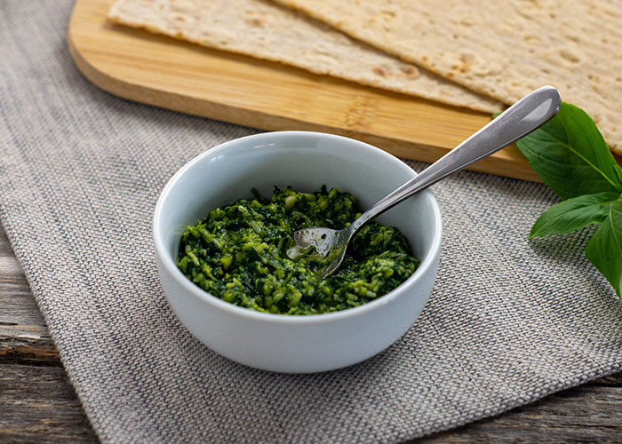 Thai basil pesto in a round white dish with a stainless steel spoon in front of a bamboo board with flatbread next to a sprig of thai basil on a grey placemat all on a wooden surface
