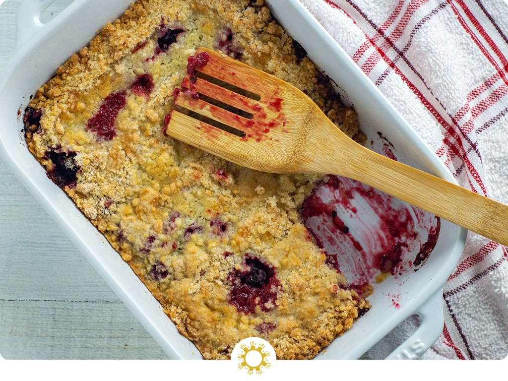 Blackberry cobbler in a white casserole dish with a wooden spoon next to a red and white towel all on a white wooden surface (with logo overlay)