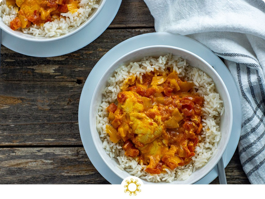Instant pot butter chicken over white rice in a round white bowl on a round white plate with a stainless steel fork next to a white and gray towel with a second bowl behind all on a wooden surface (with logo overlay)