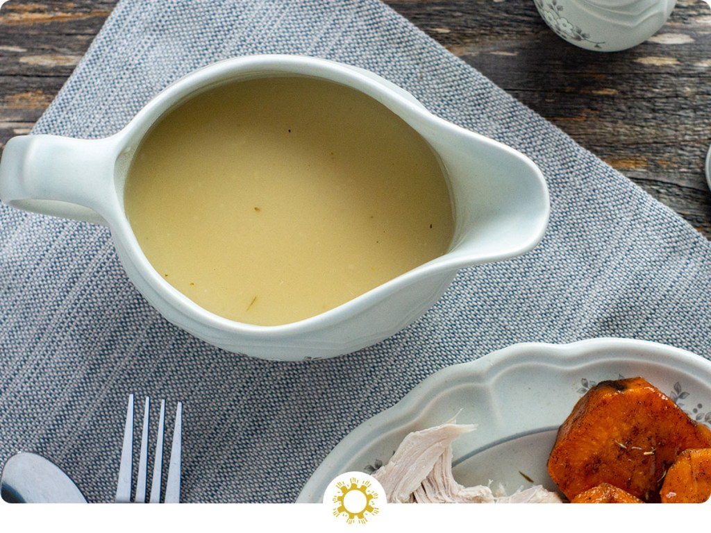 Overhead view of turkey gravy in a white gravy boat next to a plate with turkey and yams on a grey placemat on a wooden surface (with logo overlay)