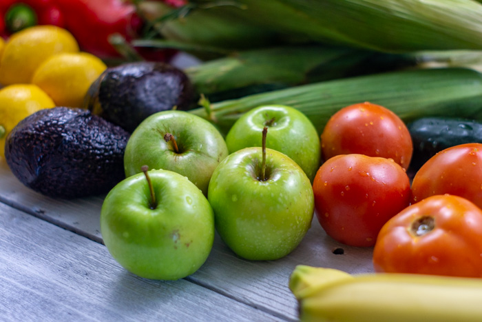 Close-up of apples, tomatoes, avocados, and other fruits and vegetables on a white wooden surface