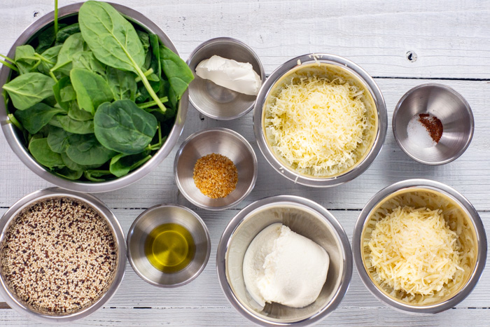 Ingredients for four cheese spinach pasta in stainless steel bowls on a white wooden surface