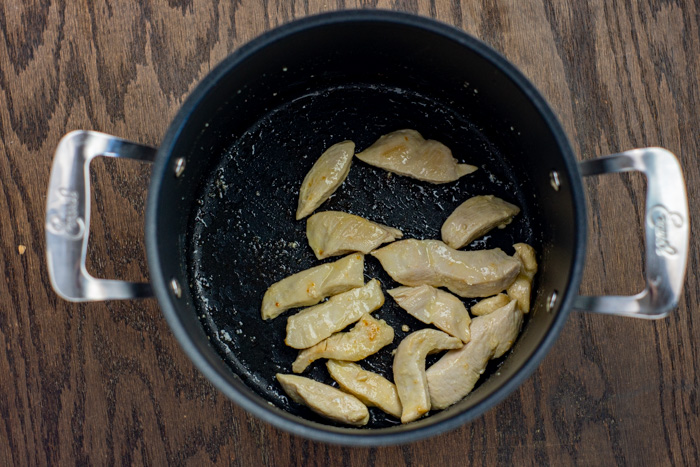Sliced cooked chicken in a stockpot on a wooden surface