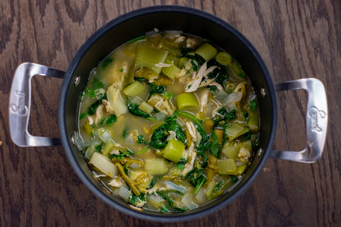 Shredded chicken added to diced vegetables and broth in a large stockpot on a wooden surface