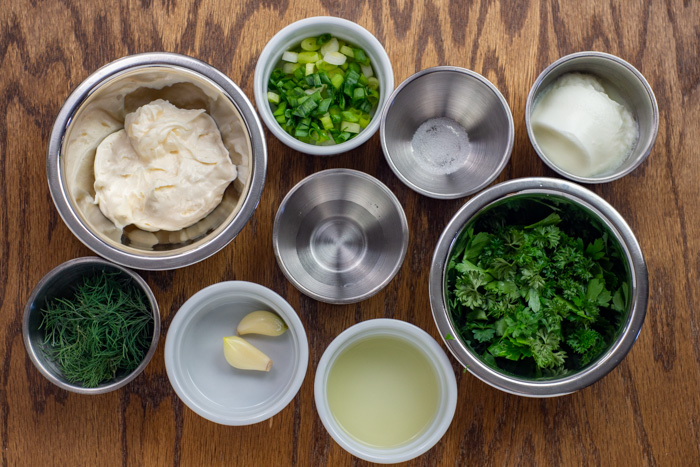 Ingredients for green goddess dressing in stainless steel and white round bowls on a wooden surface