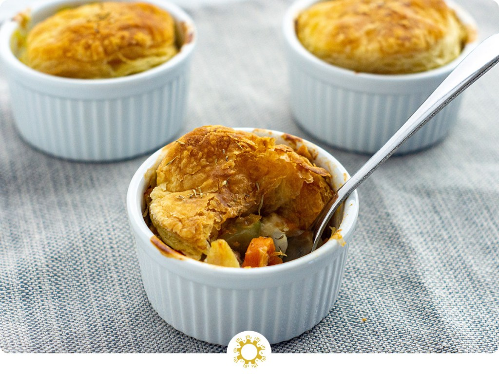 3 mini chicken pot pies in round white ramekins with a stainless steel spoon on a grey cloth surface (with logo overlay)