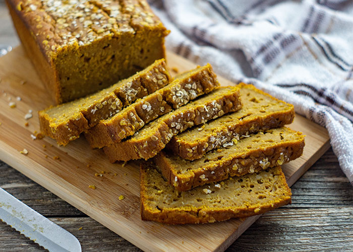 Sliced pumpkin maple bread on a bamboo tray with a white and brown towel behind all on a wooden surface