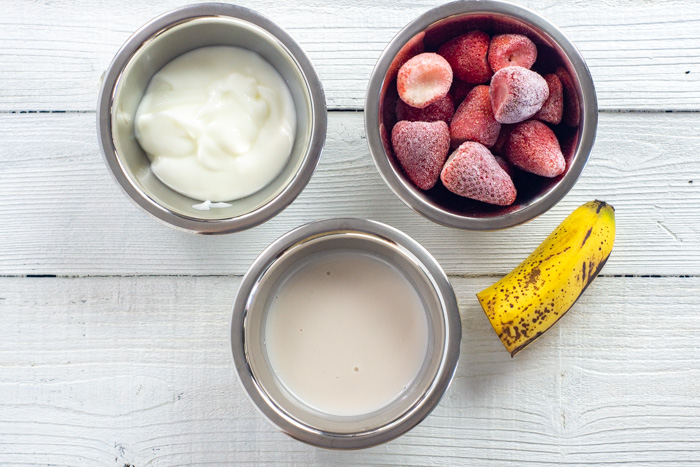 Ingredients for a strawberry banana smoothie in stainless steel bowls on a white wooden surface