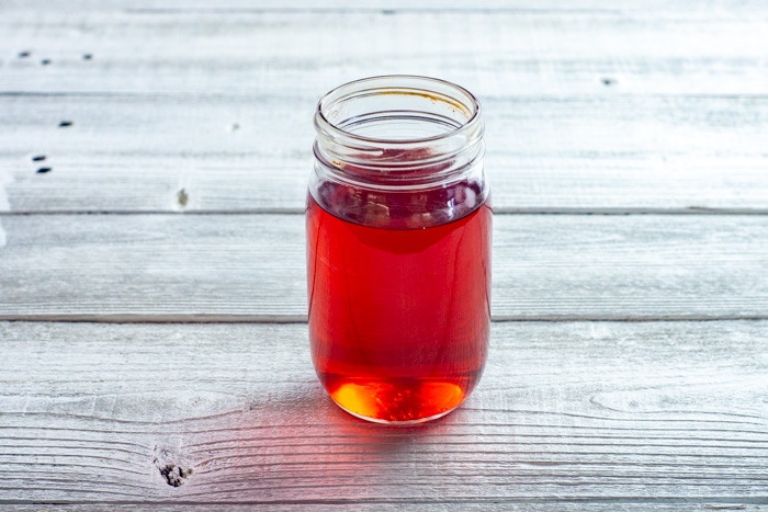 Cranberry simple syrup for Christmas Morning Sunrise Cocktail in a mason jar on a white wooden surface