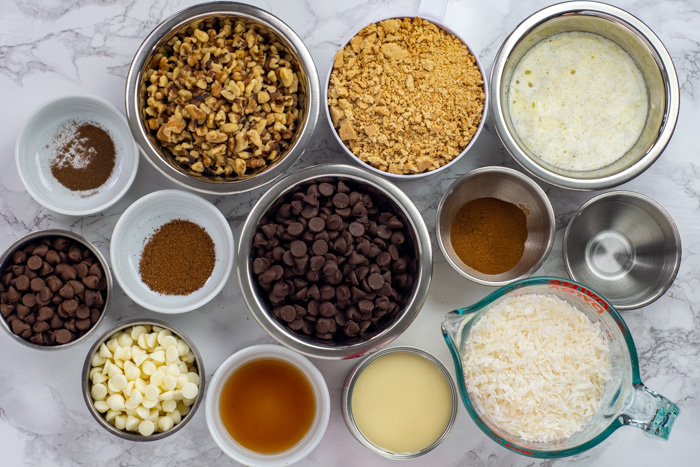 Ingredients for triple chocolate coconut bars on a white and grey marble surface