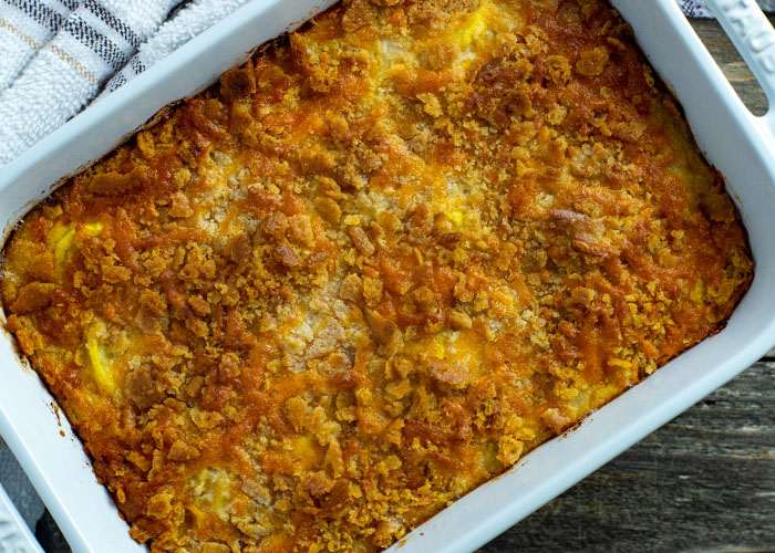 Yellow squash casserole in a white casserole dish with a white and brown towel behind all on a wooden surface