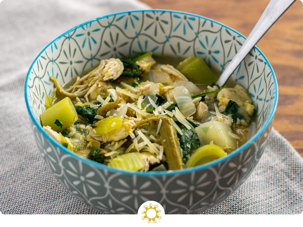 Green chicken soup garnished with parmesan cheese in a white and blue bowl with a stainless steel spoon on a grey placemat on a wooden surface (with logo overlay)