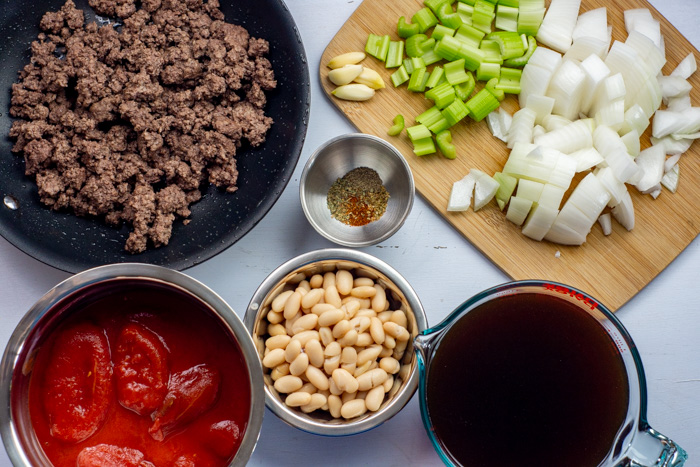 Ingredients for pasta fagioli soup: browned ground beef, garlic, diced celery and onion, beef broth, white beans, and whole peeled tomatoes
