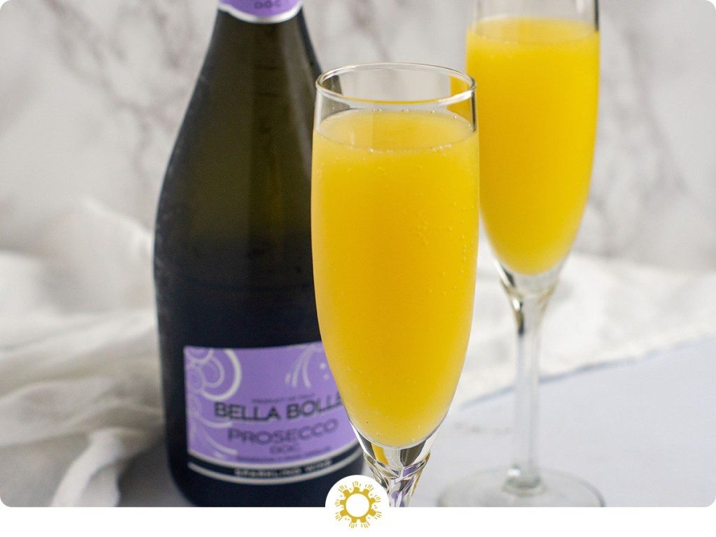 Two prosecco mimosa drinks in champagne flutes in front of a bottle of prosecco with a white towel behind all on a white surface (with logo overlay)