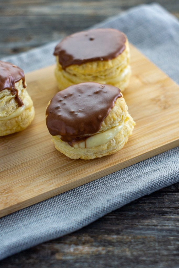 Three Boston Cream Puff Pastries on a bamboo tray on a grey tablecloth on a wooden surface (vertical)