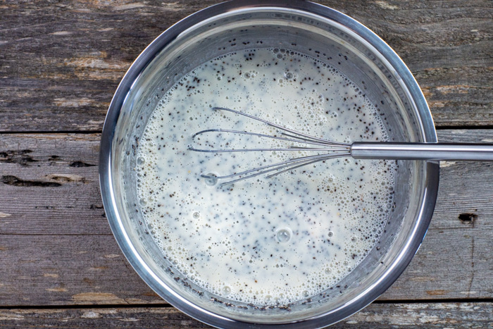 Whisked chia pudding with a wire whisk in a stainless steel bowl on a wooden surface