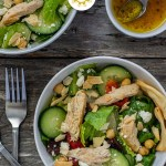 Two bowls of Greek chicken salad next to a smaller bowl of dressing with a spoon and a fork next to the bowls all on a wooden surface (with title overlay)