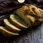 Irish Soda Bread with a few slices cut off with a brown and white towel behind all on a wooden surface (with title overlay)
