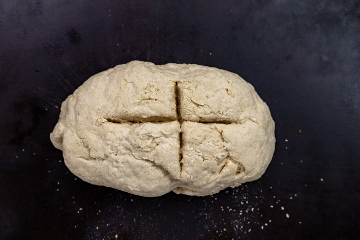 Soda bread dough with a cross cut into it on a baking stone