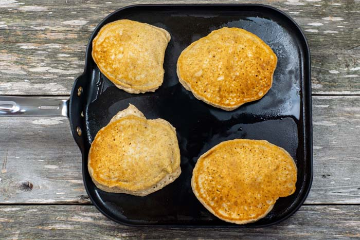 Cooked banana bread pancakes on a flat skillet on a wooden surface