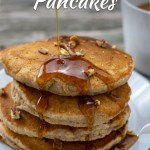 Pile of banana bread pancakes topped with chopped pecans on a round white plate with syrup being dripped on top with a white mug of coffee behind all on a wooden surface (with title overlay)