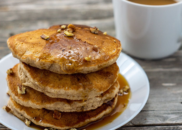 Pile of banana bread pancakes topped with chopped pecans on a round white plate with syrup being dripped on top with a white mug of coffee behind all on a wooden surface