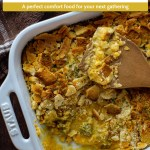 Broccoli and cheese casserole topped with crushed crackers with a wooden spoon in a white casserole dish with a brown and white cloth all on a wooden surface (with vertical overlay)