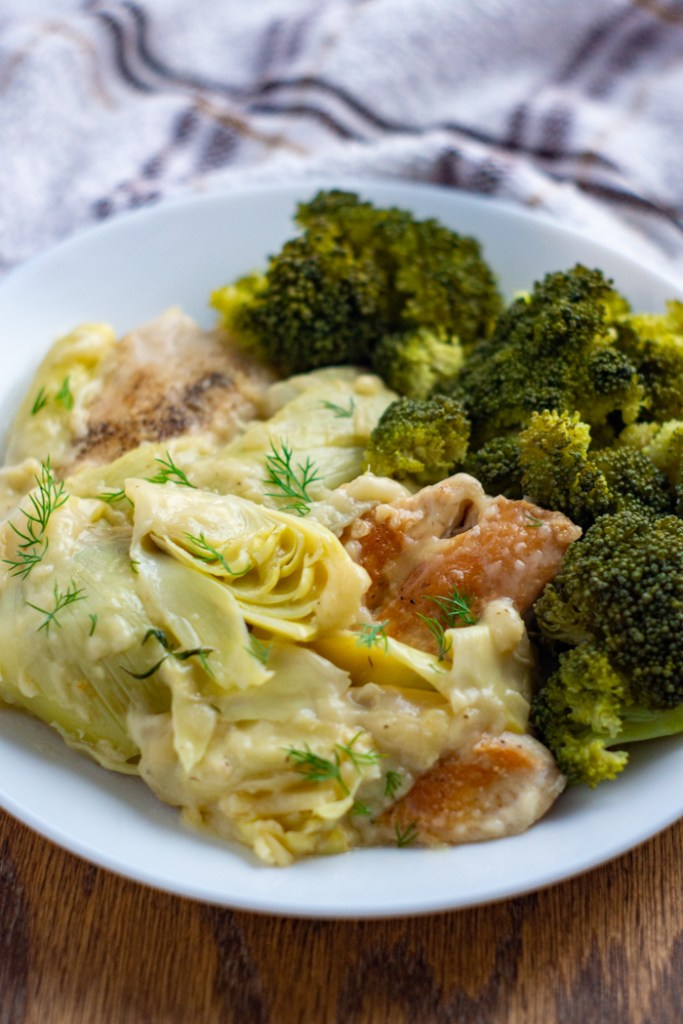 Chicken with artichoke sauce garnished with dill next to steamed broccoli on a round white plate with a white and brown towel behind all on a wooden surface (vertical)