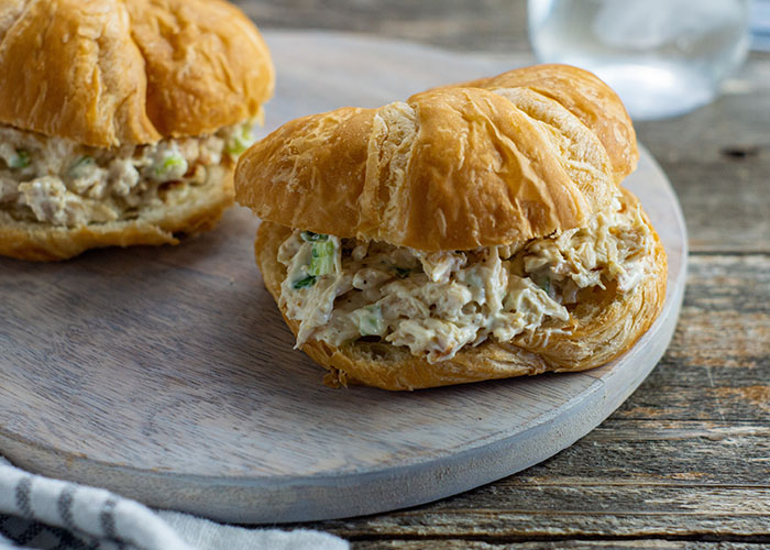 Two chicken salad sandwiches on a grey tray on a wooden surface