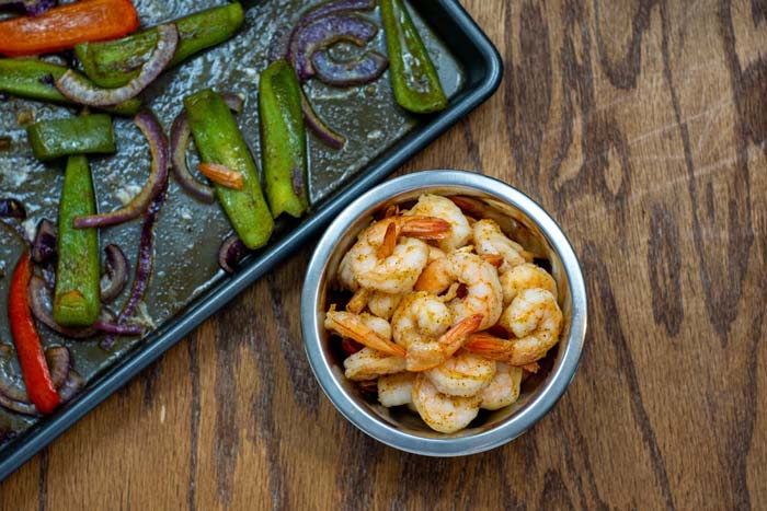 Cooked shrimp in a small stainless steel bowl next to a sheet pan with roasted vegetables on a wooden surface