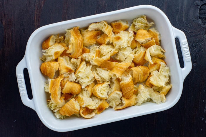Torn up croissant rolls in a white casserole dish on a dark wooden surface